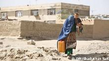 Woman carries water canister in one hand and a child in the other