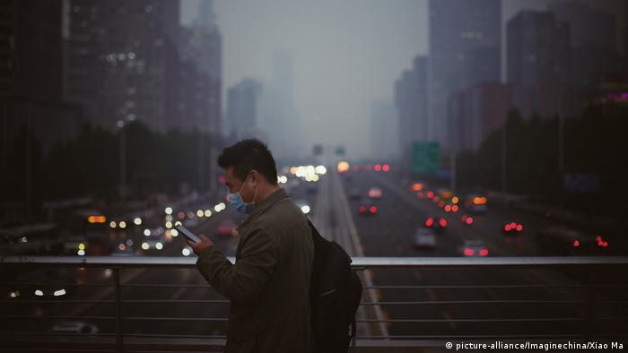 Man with a face mask looking at smartphone, against background of a smog-covered road in Beijing