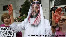 10.10.218 Security personnel are seen in the background as David Barrows, center, with Code Pink, wears a mask of Saudi Arabia Crown Prince Mohammed bin Salman during a protest outside of Saudi Arabia's Embassy about the disappearance of Saudi journalist Jamal Khashoggi, Wednesday, Oct. 10, 2018, in Washington. (AP Photo/Jacquelyn Martin)  
