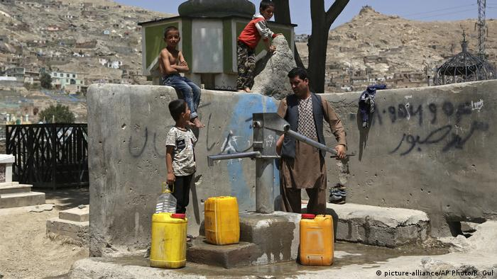 A man and three children fill large yellow canisters at a public water pump