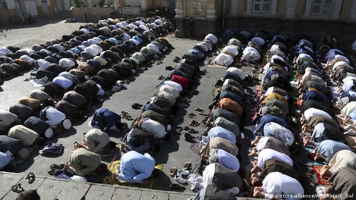 Rows of Muslim men kneeling down in prayer