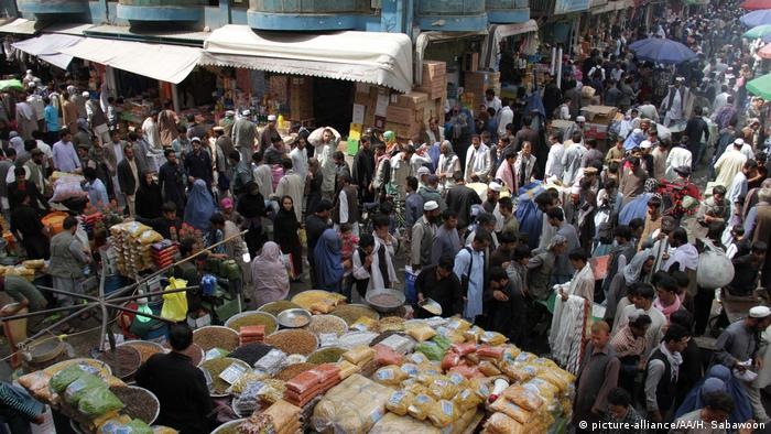 Hundreds of people mill around a basar in Kabul