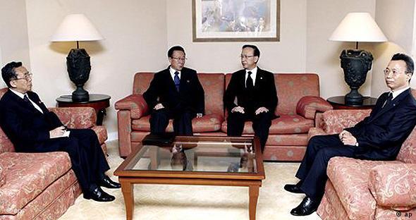 Hyun (M. r.) und Kim (M. l.) in einem Hotelzimmer, rechts und links von ihnen unbekannte Begleiter (Foto: AP)