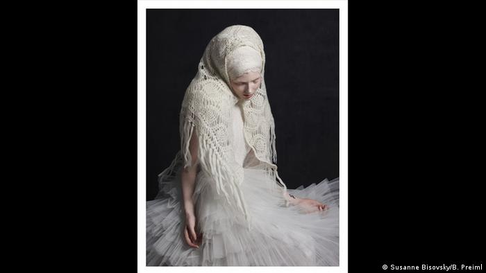 A woman wearing a lacey white headscarf and tulle skirt looks downwards