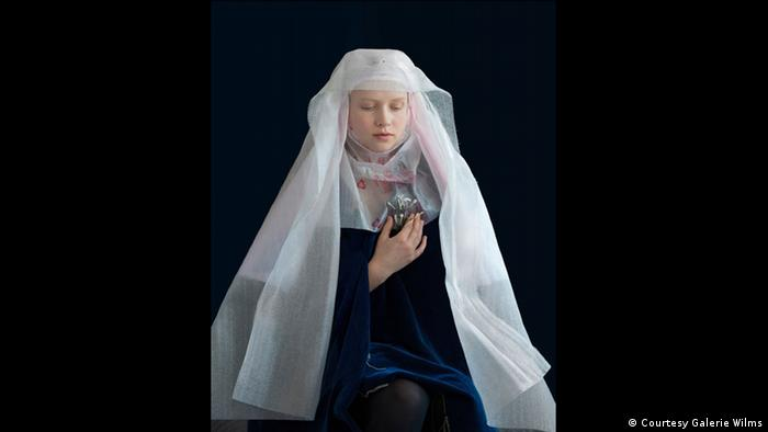 A photograph shows a woman dressed lik ea nun but whose veil is made of recycled packaging materials