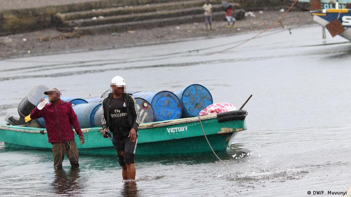 Two men walking in shallow water next to a boat carrying large oil drums in Cameroon's port of Idenau (DW/F. Muvunyi )