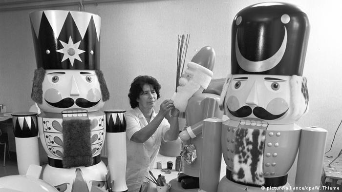 A black-and-white photo of a woman working on huge nutcrackers (picture-alliance/dpa/W. Thieme)