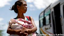 Yoenny Cazorla, an undocumented Venezuelan migrant, looks at a bus driving past while she rests close to Los Patios, Colombia August 25, 2018. Cazorla, from the violent Venezuelan city of Maracay, was walking with relatives to the Colombian city of Medellin. REUTERS/Carlos Garcia Rawlins SEARCH MIGRANT TACHIRA FOR THIS STORY. SEARCH WIDER IMAGE FOR ALL STORIES.