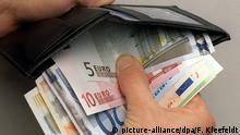 ILLUSTRATION - 29.11.2001, Frankfurt:Main: Ein Mann nimmt Euro-Geldscheine aus einer Geldbörse. (zu «Armut trotz Job: 131000 Beschäftigte in Sachsen gefährdet » vom 17.10.2018) Foto: Frank Kleefeldt/dpa +++ dpa-Bildfunk +++ | Verwendung weltweit