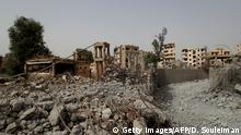 A picture taken on October 15, 2018, shows a cleared path amidst the rubble of buildings in the northern Syrian city of Raqa. - The fighting ended on October 17 last year, when the city finally fell to the Syrian Democratic Forces, which then handed it over to the Raqa Civil Council (RCC) to govern. Rights group Amnesty International estimates around 80 percent of Raqa was devastated by fighting, including vital infrastructure like schools and hospitals. (Photo by Delil SOULEIMAN / AFP) (Photo credit should read DELIL SOULEIMAN/AFP/Getty Images)