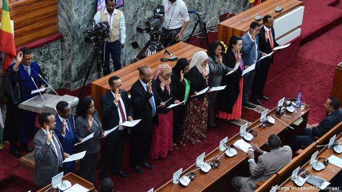 Members of Ethiopia's new cabinet raise their hands as they take their oath of office at the parliament