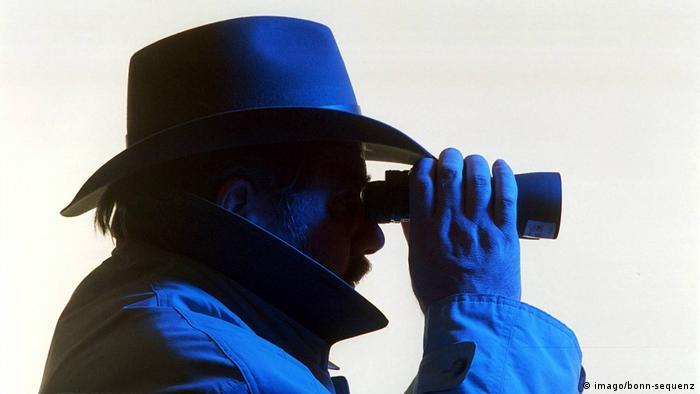 Muškarac sa šeširom na glavi gleda dalekozorom