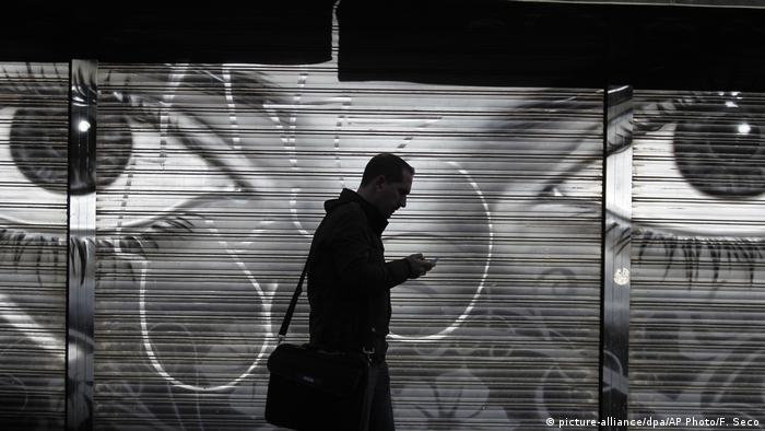 Black-and-white photo illustration of a backlit person walking past a screen showing a closeup of someone's eyes