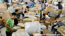 Chinese workers sort online purchases in a warehouse