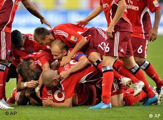 Gute Leistung, guter Weg: Der HSV feiert seinen Sieg beim Meister. (Quelle: AP Photo/Axel Heimken)