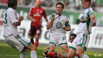 Die Wölfe Barzagli, Riether, Madlung (v.li.) und der Hamburger Guerrero (unten) im Kampf um den Ball. (Quelle: AP Photo/Axel Heimken)