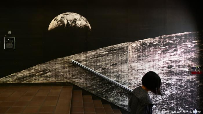 A woman walks past an image of the moon in a stairway (Getty Images/AFP/F. J. Brown)