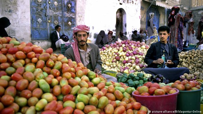Two men in Sanaa at a market stand behind piles of fruit and vegetables