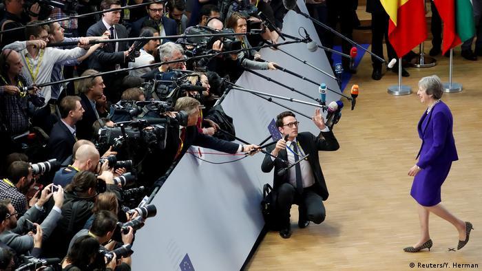 Theresa May walks towards press cameras