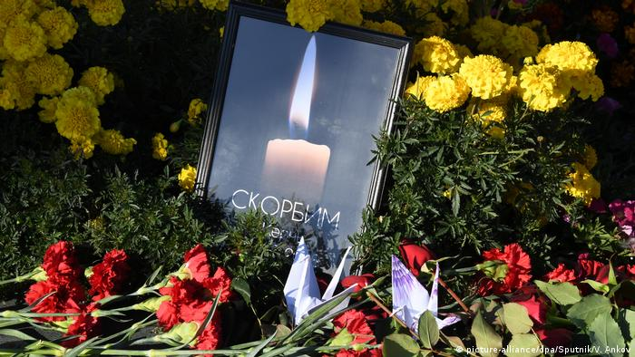 A candle burns among flowers as a mourning momento