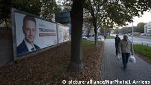 A billboard shows a candidate for election in Poland's local vote as a man walks by it (picture-alliance/NurPhoto/J. Arriens)