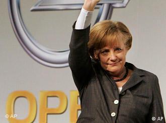 Angela Merkel waving in front of an Opel logo.