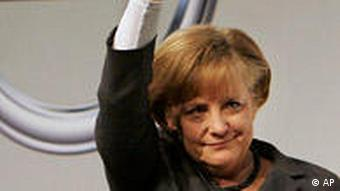 Chancellor Merkel waves in front of an Opel logo
