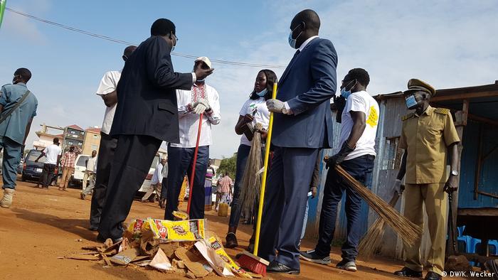 Juba's mayor, deputy mayor and army officials hold brooms and talk