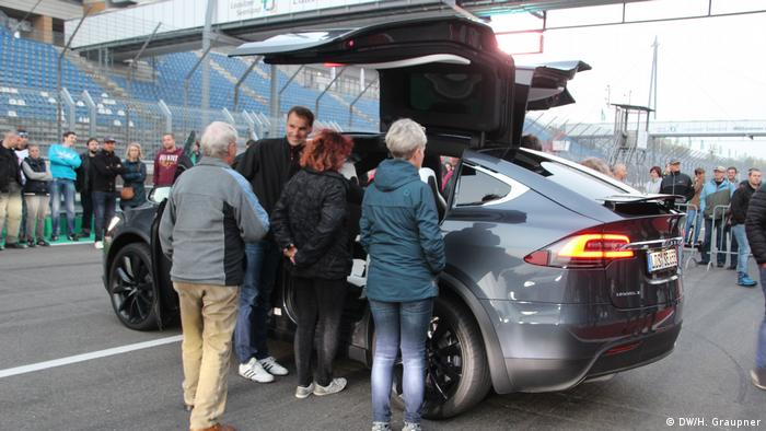 Lusatians looking at a Tesla car