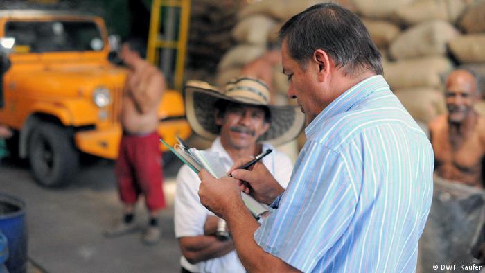 Ein Kaffeebauer in Kolumbien schreibt auf einen Block