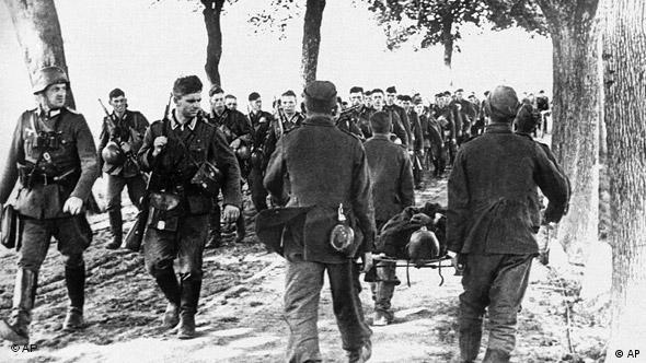 German troops march past Polish prisoners of war during World War II