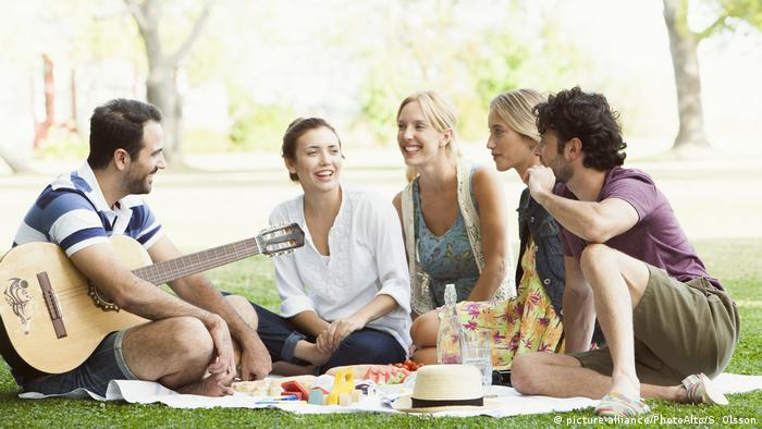 A group of people sitting in a park (picture-alliance/PhotoAlto/S. Olsson)