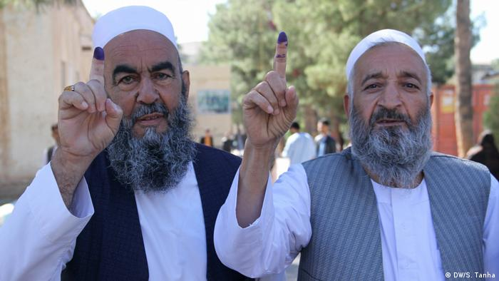 Two Afghan men hold up inked fingers showing that they voted