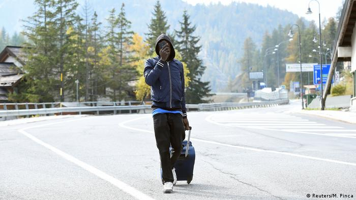 A migrant walks through Claivere on the road with his hand in front of his face