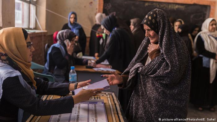 An old woman hands over her voting ballot to a young election worker