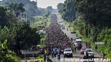 Thousands of migrants march along a highway