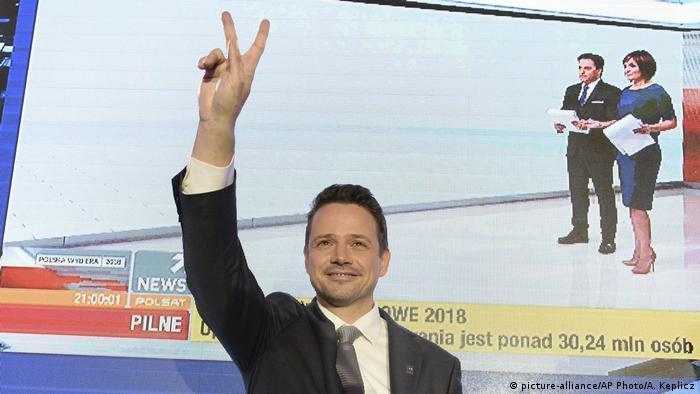 Rafal Trzaskowski levanda a mão, fazendo o V da vitória