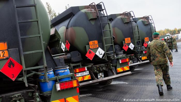 A soldier walks past German fuel tanks during NATO's Trident Juncture exercise in Norway (picture-alliance/dpa/M. Assanimoghaddam)
