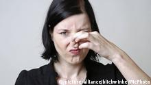 Symbolbild Frau hält sich Nase zu