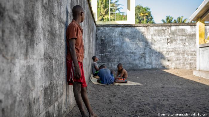 A young man leans against a wall and faces away from the camera in the yard of a juvenille prison in Madagascar. Three other boys are huddled together in the background.