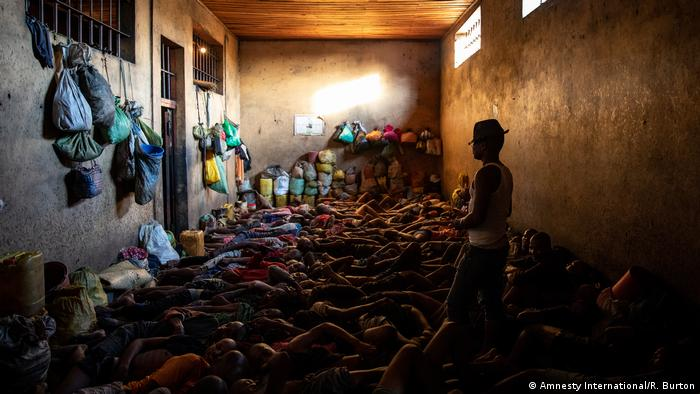 Dozens of men lie on the ground of an overcrowded prison cell in Madagascar
