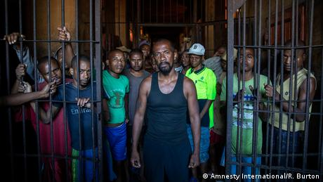 A group of pre-trial detainees in Madagascar stand behind half-opened prison bars, facing the cameria
