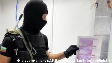 A police officer holds counterfeit five hundred Euro bills (picture-alliance/AP Photo/Bulgarian Interior Ministry)