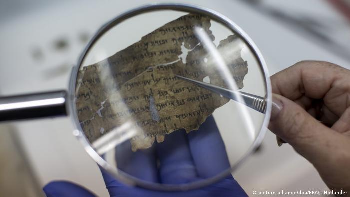 A restorer works on fitting pieces of the original Dead Sea Scrolls in place