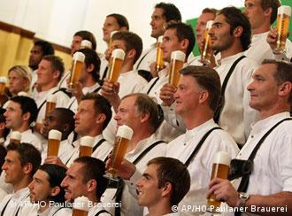 Bayern Munich players and coach van Gaal pose holding beer glasses and wearing Lederhosen