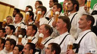 Bayern Munich players pose in lederhosen with glasses of beer