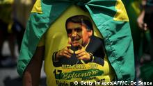 Supporters of Brazil's presidential right-far candidate Jair Bolsonaro take part in a rally in Copacabana, Rio de Janeiro, on October 21, 2018. - Barring any last-minute upset, Brazil appears poised to elect Jair Bolsonaro, a populist far-right veteran politician, as its next president in a week's time. (Photo by CARL DE SOUZA / AFP) (Photo credit should read CARL DE SOUZA/AFP/Getty Images)