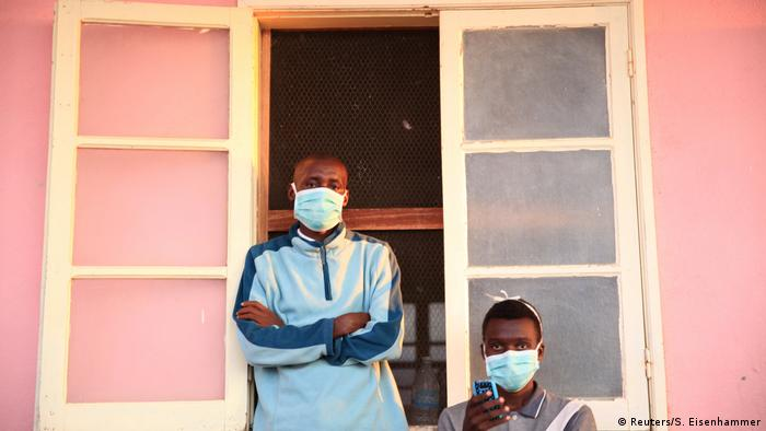 Tuberculosis patients, wearing masks to stop the spread of the disease, stand outside a hospital in Angola (Reuters/S. Eisenhammer)