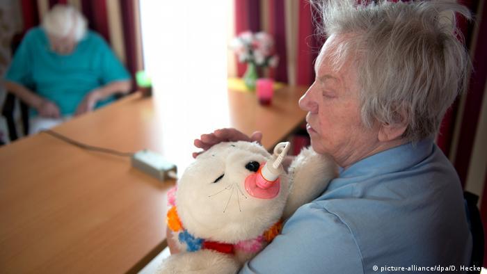 Eine Frau drück eine weiße Kuscheltierrobbe an sich und streichelt sie (Foto: Picture Alliance)
