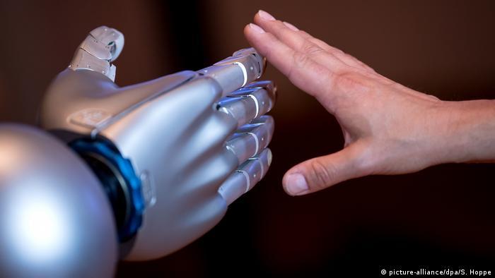 Eine menschliche Hand und eine Roboterhand berühren sich an den Fingern (Foto: Picture Alliance)
